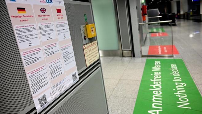 Cartel en varios idiomas con información sobre el coronavirus de Wuhan, en la terminal de llegadas del aeropuerto de Duesseldorf, Alemania.