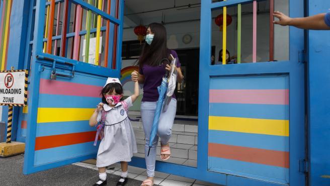 Una mujer y su hija salen del colegio en Manila (Filipinas).