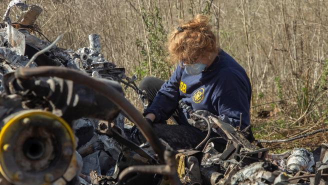 La investigadora de la NTSB Carol Hogan examina los restos del accidente.