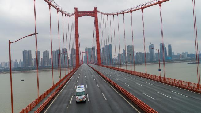 Una ambulancia circula por un puente vacío este domingo en Wuhan.