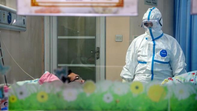 Un médico atiende a un paciente afectado por el coronavirus de Wuhan, en un pabellón de aislamiento de un hospital de la ciudad china.
