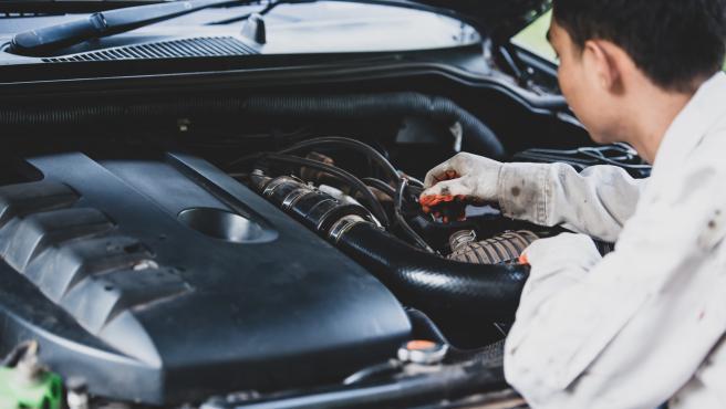 Mecánico reparando el motor de un coche.