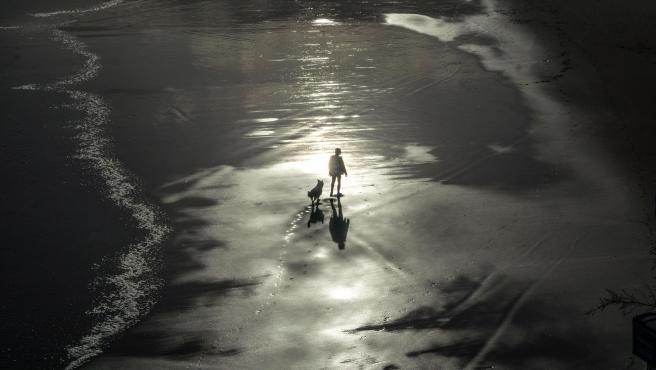 Un hombre pasea con su perro por la playa del Sardinero en Cantabria.