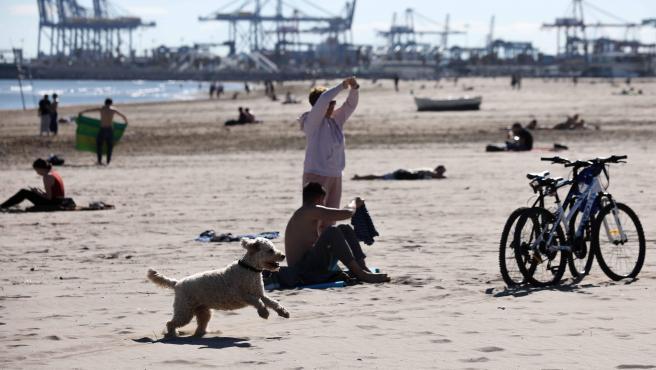Varias personas disfrutan de un día de calor en la playa de la Malvarrosa de Valencia.