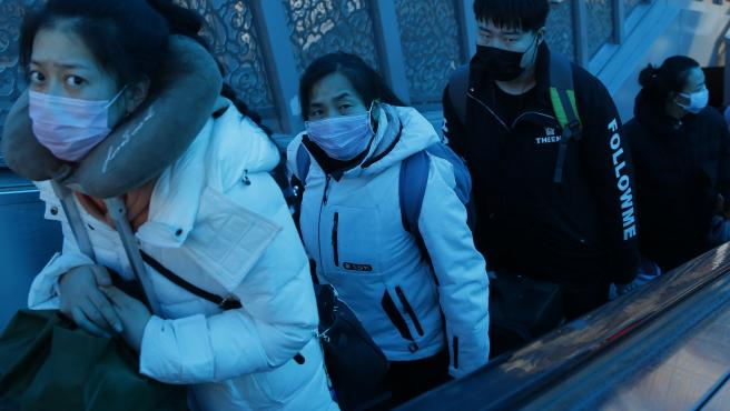 Varios ciudadanos chinos con mascarillas suben una escalera mecánica en la Estación Central de Pekín, China.