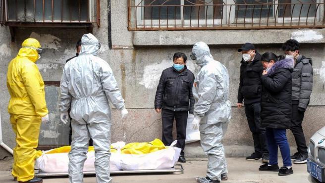 Empleados de una funeraria se hacen cargo del cuerpo de una persona que falleció en su casa víctima del coronavirus nCoV, en Wuhan, China.