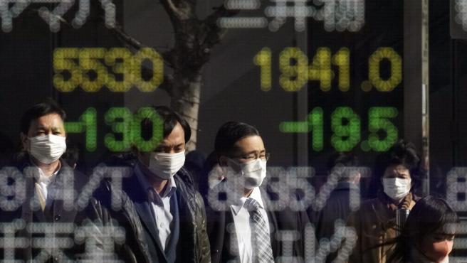 Los peatones que llevan máscaras se reflejan en un panel de indicadores del mercado de valores en Tokio.