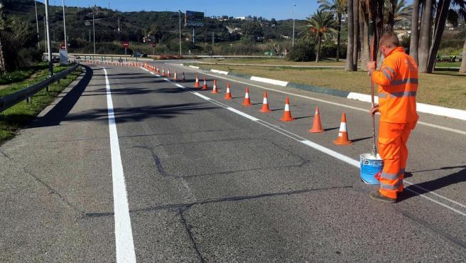 Un operario mejora la señalización de las avenidas de Estepona