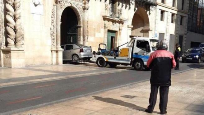 La grúa retira un coche aparcado en el Ayuntamiento de Alicante.