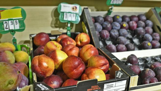 Fruta variada: caja de manzanas, caja de ciruelas y caja de mangos en un mercado de Madrid.