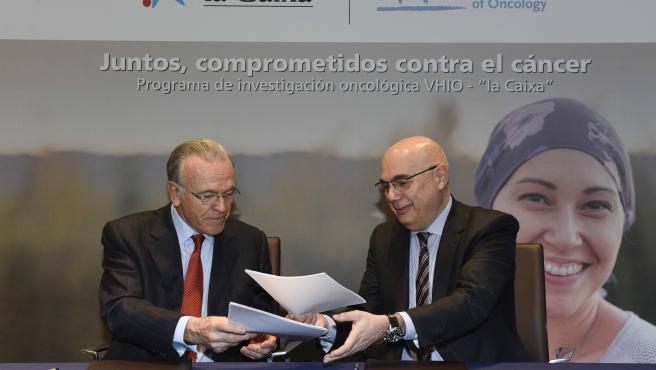 Isidro Fainé y Josep Tabernero, firman el convenio.