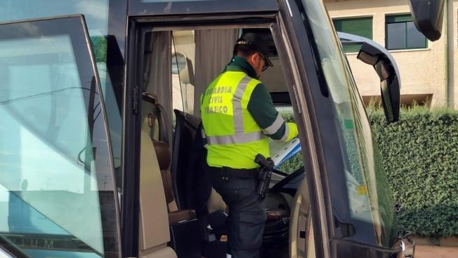 Un agente de la Guardia Civil inspecciona un autobús