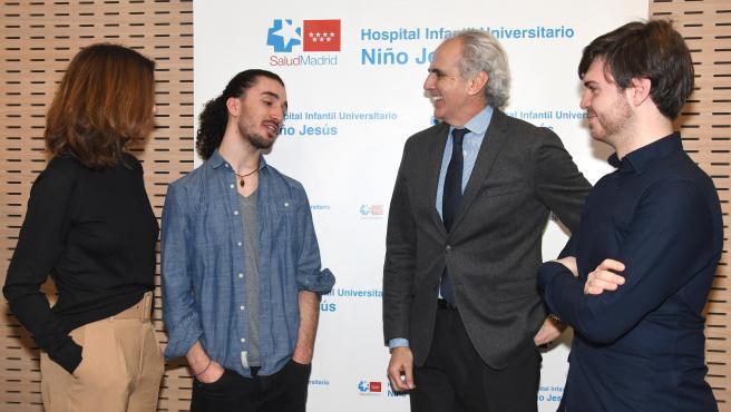 El consejero de Sanidad, Enrique Ruiz Escudero, charla con Carlos Clerencia y Sergio Palomeque, dos jóvenes supervivientes de cáncer pediátrico.