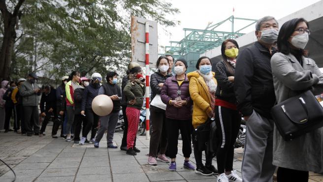 Cola de personas comprando mascarillas en Vietnam