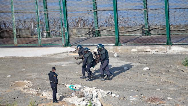 Cuatro agentes de la Guardia Civil trasladan a la fuerza a un migrante para su devolución en caliente a Marruecos tras haber intentado saltar la valla de Ceuta.