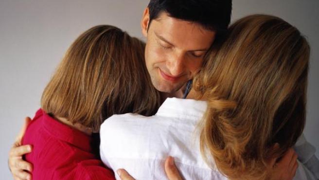 Un hombre abraza a dos mujeres.