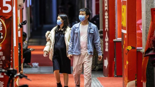 Pareja con máscaras por el coronavirus durante la celebración de San Valentín.