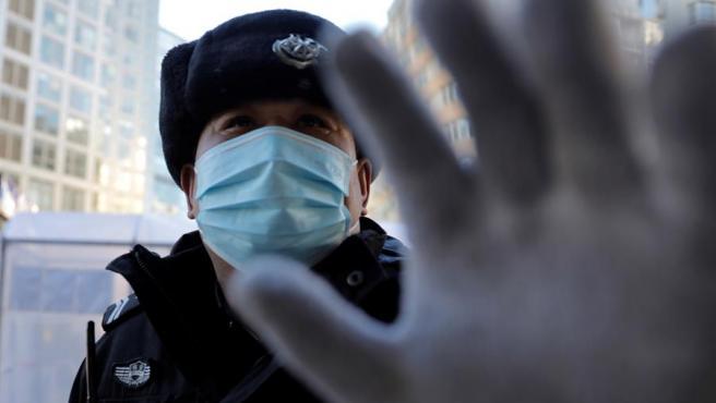 Un guardia de seguridad intenta tapar una cámara frente a una instalación de desinfección del coronavirus COVID-19 a la entrada de un complejo residencial en Pekín, China.