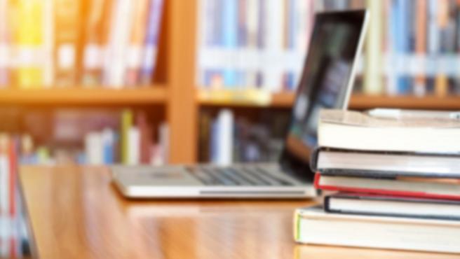 Ordenador portátil en biblioteca, estudiar, estudiante, centro escolar, libros