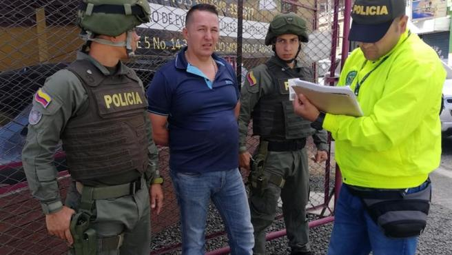 Carlos Alberto Salazar, conocido como 'El señor de la bata', custodiado por la Policía en Bogotá (Colombia), tras ser capturado.