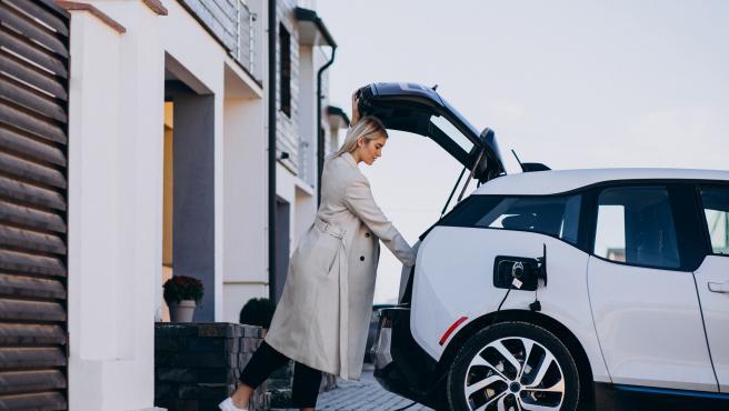 Mujer cargando su coche eléctrico en su casa.