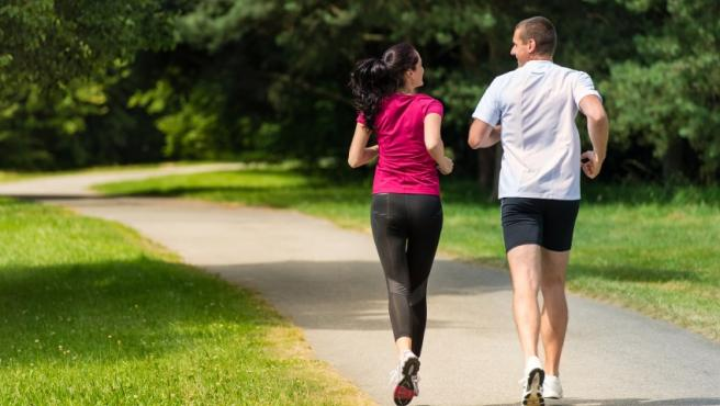 Rear view of Caucasian female and male runners outdoors