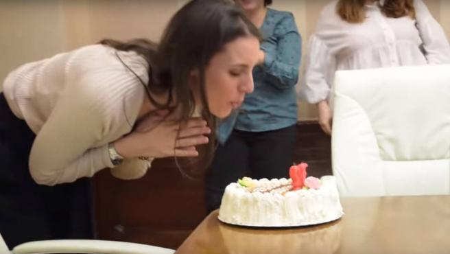 Irene Montero sopla las velas de una tarta de cumpleaños.