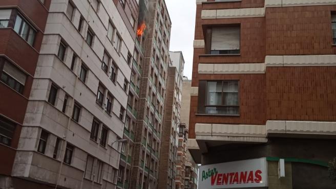 Los bomberos sofocando un fuego en un piso en Gijón
