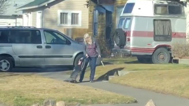 Mujer pasando una aspiradora en la calle