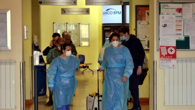 os trabajadores de salud (de frente, en azul) con máscaras faciales caminan con equipo médico portátil en un pasillo del Hospital Cívico de Codogno, donde la sala de emergencias ha sido cerrada como Una medida de precaución