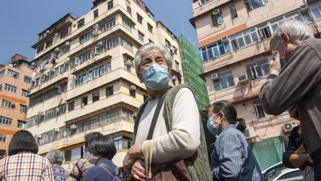 Un grupo de personas hace cola para conseguir mascarillas gratis en Hong Kong.