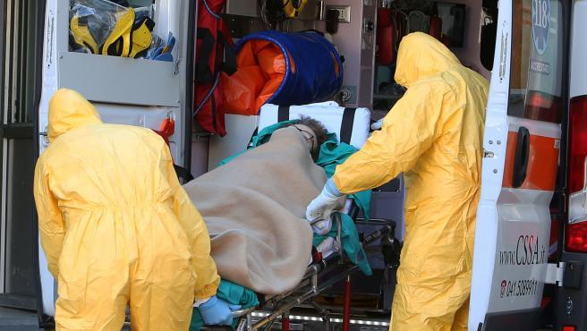 Trabajadores sanitarios protegidos con trajes contra el coronavirus trasladan a una paciente al hospital de Padua, al norte de Italia.