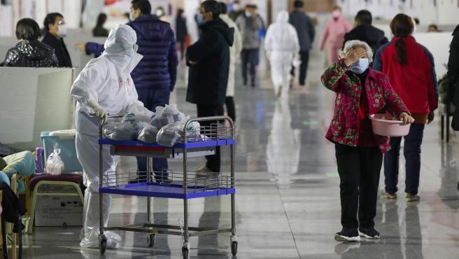 Una enfermera distribuye medicamentos a pacientes en un hospital temporal situado en el gimnasio Tazihu en Wuhan, epicentro del coronavirus chino.
