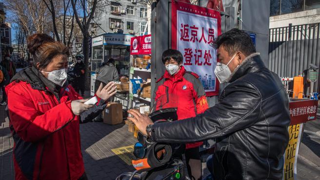 Voluntarios de seguridad pública en Pekín con máscaras faciales protectoras detienen a un hombre en moto para verificar la temperatura de su cuerpo y la tarjeta de entrada a un área residencial.