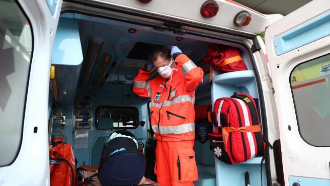 Un trabajador sanitario se pone una mascarilla.en Brescia.