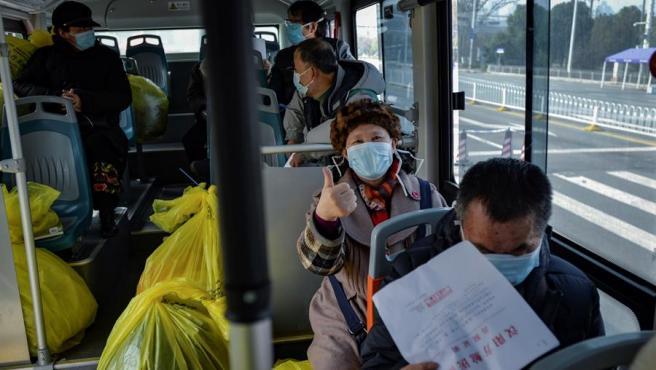 Pacientes del coronavirus COVID-19 dados de alta abandonan un hospital en Wuhan, China, para ser puestos en cuarentena en otra instalación sanitaria.