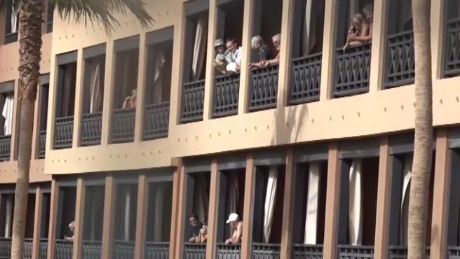 Varios huéspedes se asoman a los balcones del hotel en cuarentena.