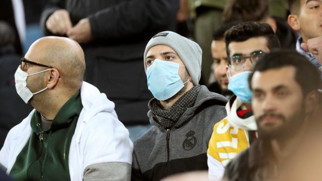 Varios aficionados del Real Madrid con mascarilla