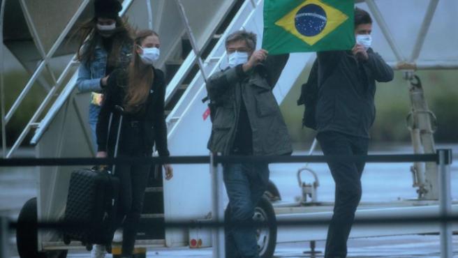 Pasajeros salen de uno de los aviones en los que fueron repatriados de la ciudad china de Wuhan 34 brasileños y sus parientes, tras aterrizar en una base de Anápolis (Brasil).
