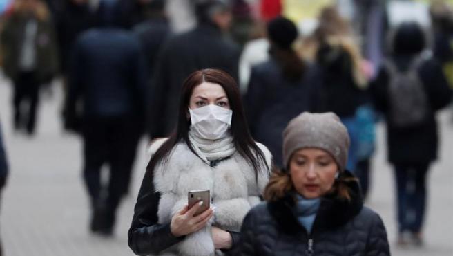 Una mujer camina con una mascarilla en el centro de Moscú, Rusia.