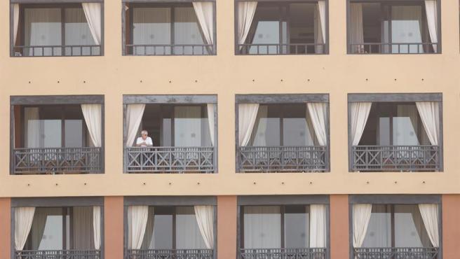 Un huésped se asoma a un balcón del hotel del municipio tinerfeño de Adeje, donde se registraron casos del coronavirus de Wuhan.