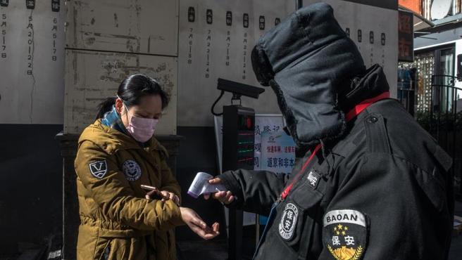 Un guardia toma la temperatura de una mujer en Pekín, como medida preventiva ante la epidemia del coronavirus COVID-19.