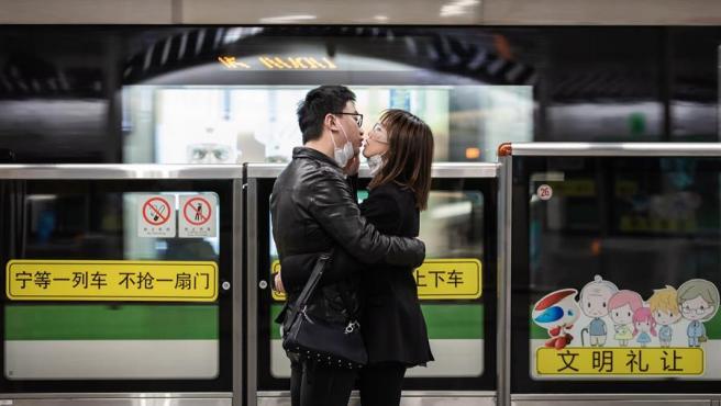 Una pareja se besa con sus mascarillas bajadas, mientras espera un tren en la estación de la Plaza del Pueblo en Shanghai, China.