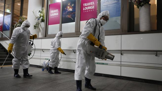 Trabajadores sanitarios desinfectan una estación de metro en Seúl.