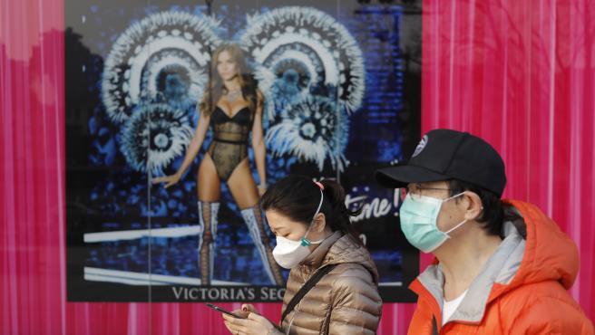 Dos ciudadanos caminan por las calles de Pekín en pleno brote de coronavirus.