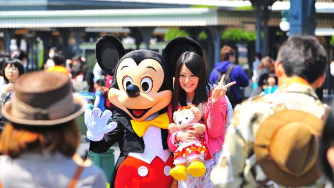 Visitantes posan para una foto con Mickey Mouse en Tokyo Disneyland en Urayasu, Japón.
