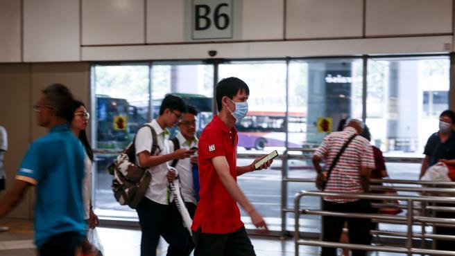 Un hombre con mascarilla pasea por una estación de autobuses en Singapur.
