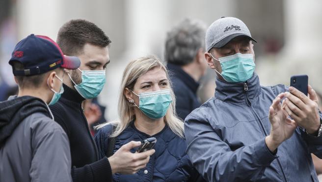 Varios asistentes llevan mascarillas para protegerse del coronavirus mientras asisten a la oración del Angelus, oficiada por el papa, en la plaza de San Pedro del Vaticano.