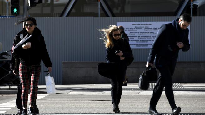 Tres personas caminan por Madrid con la presencia de la borrasca Jorge que desde el sábado se hace notar en la península dejando rachas muy fuertes de viento, lluvias y un frente frío, en Madrid (España), a 2 de marzo de 2020.