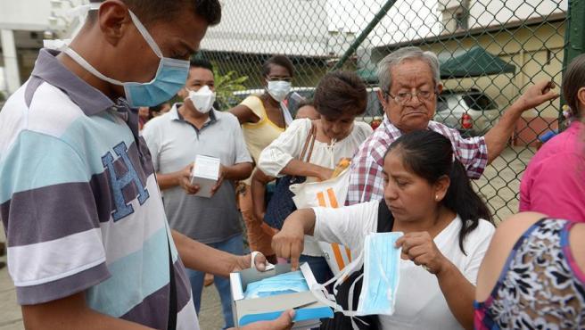 Ciudadanos compran mascarilllas a un vendedor ambulante, en Guayaquil (Ecuador).